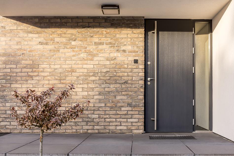 Black door with red brick exterior
