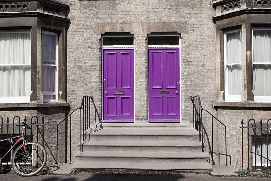 Two Identical Purple Wooden Doors on Grey Exterior